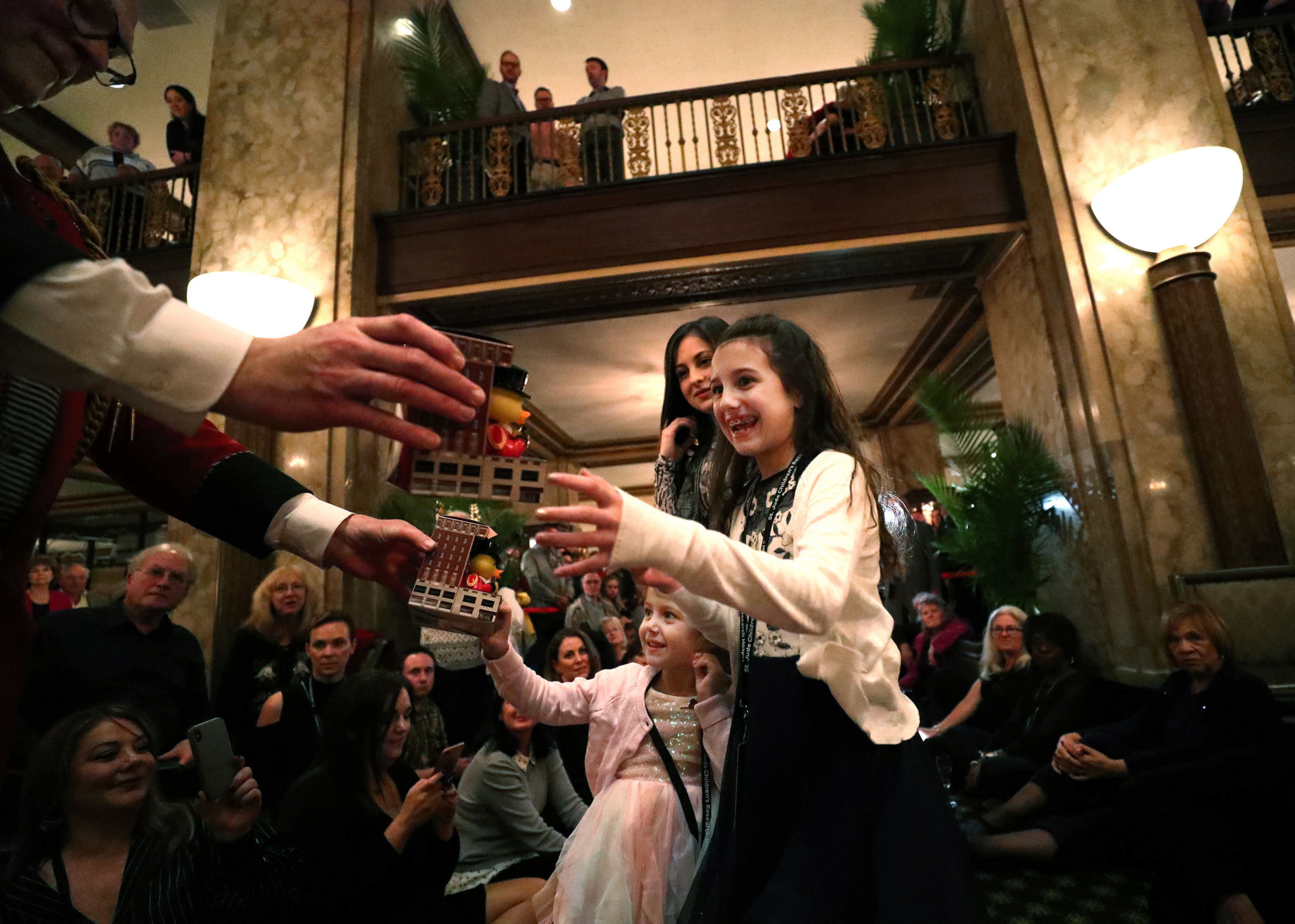 <strong>Peabody duckmaster and hotel historian Doug Weatherford hands rubber duck gifts to special guests Lucy Malouf (left), 4, Shelby Malouf (center), 15, and Charley Malouf (right), 9, on Wednesday, Feb. 6, 2019. In conjunction with the launch of its 150th anniversary celebration, the hotel has completed an $8.5 million renovation of its grand lobby and all 464 guest rooms and suites.</strong> (Houston Cofield/Daily Memphian)