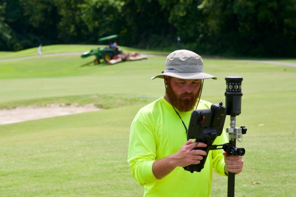 <strong>Surveyor Kevin Cannon on Thursday, Aug. 19, gathers more data near where the new Pine Hill golf house will be built. No. 1 green is behind him.</strong> (Tom Bailey/Daily Memphian)
