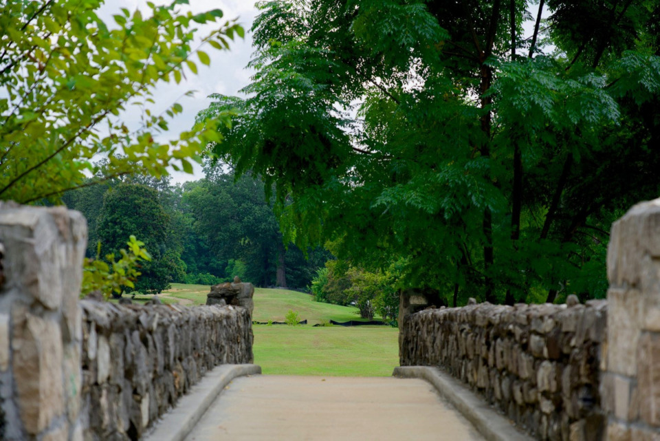 <strong>A stone-clad pedestrian bridge frames the new, growing grass on No. 7 fairway on Aug. 17 at the Overton Park golf course.</strong> (Tom Bailey/Daily Memphian file)