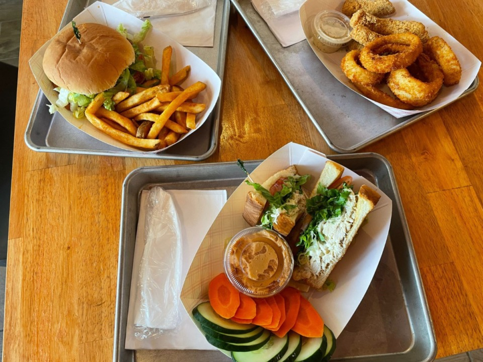 <strong>Saucy Chicken&rsquo;s homemade chicken salad sandwich (front) comes with a choice of side items, including hummus with fresh vegetables. Left: Sweet heat chicken sandiwch and right, catfish nuggets with onion rings.</strong> (Jennifer Biggs/Daily Memphian)