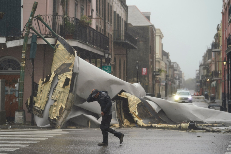 <strong>A man passes by a section of roof that was blown off of a building in the French Quarter by Hurricane Ida winds, Sunday, Aug. 29, 2021, in New Orleans.</strong> (AP Photo/Eric Gay)