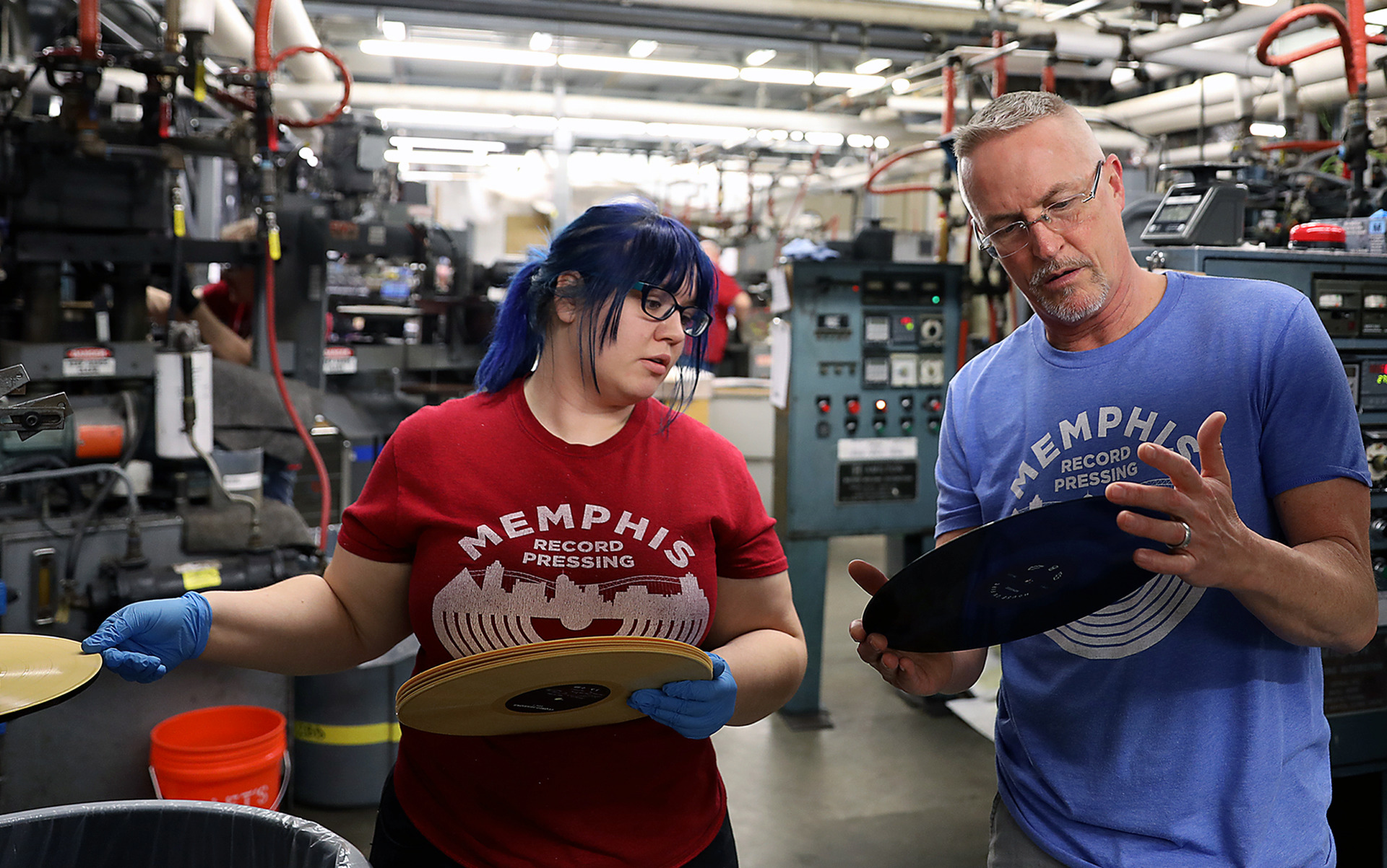 <strong>Lillia Sample and operations manager Lance Binder inspect records as they come off the presses at Memphis Record Pressing's Bartlett location. Currently, the facility produces more than 300,000 records per month, but hope to bring that number closer to 450,000 with the addition of new equipment.</strong> (Patrick Lantrip/ Daily Memphian)