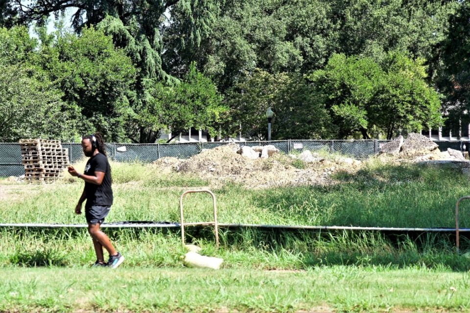 <strong>The collapse of the barrier fence along Union allowed this jogger on Thursday, Sept. 2, to stop and take a photo of the rubble where Nathan Bedford Forrest and his wife had been buried in Health Sciences Park.</strong> (Tom Bailey/Daily Memphian)