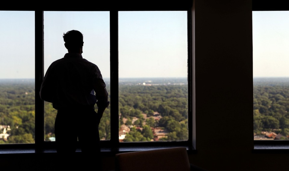 <strong>An employee looks out the window of the Clark Tower on Aug. 25, 2021 while on a work call.</strong> (Patrick Lantrip/Daily Memphian)