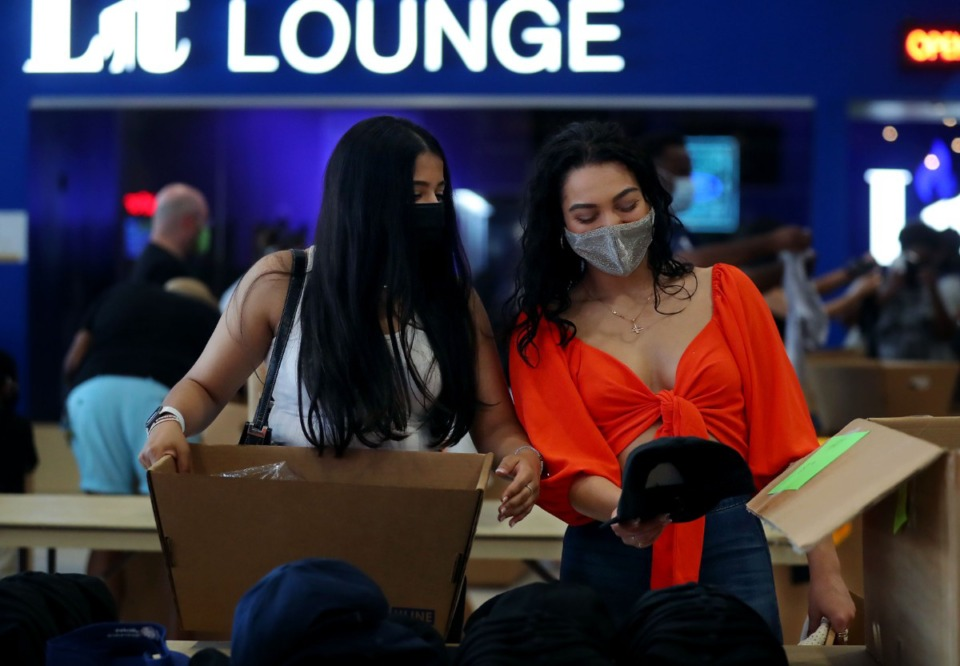 <strong>Megha Patel (left) and Danielle Husseini shop for hats at the Grizzlies Garage Sale at&nbsp; FedExForum Aug. 28, 2021.</strong> (Patrick Lantrip/Daily Memphian)