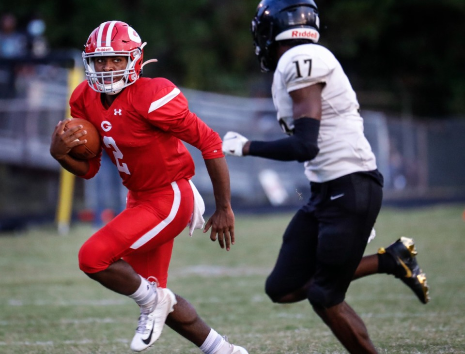 <strong>Germantown quarterback Malik Young (left) looks for lane while Whitehaven&rsquo;s Mikkal Stewart (right) closes in on Friday, Sept. 3.</strong> (Mark Weber/The Daily Memphian)