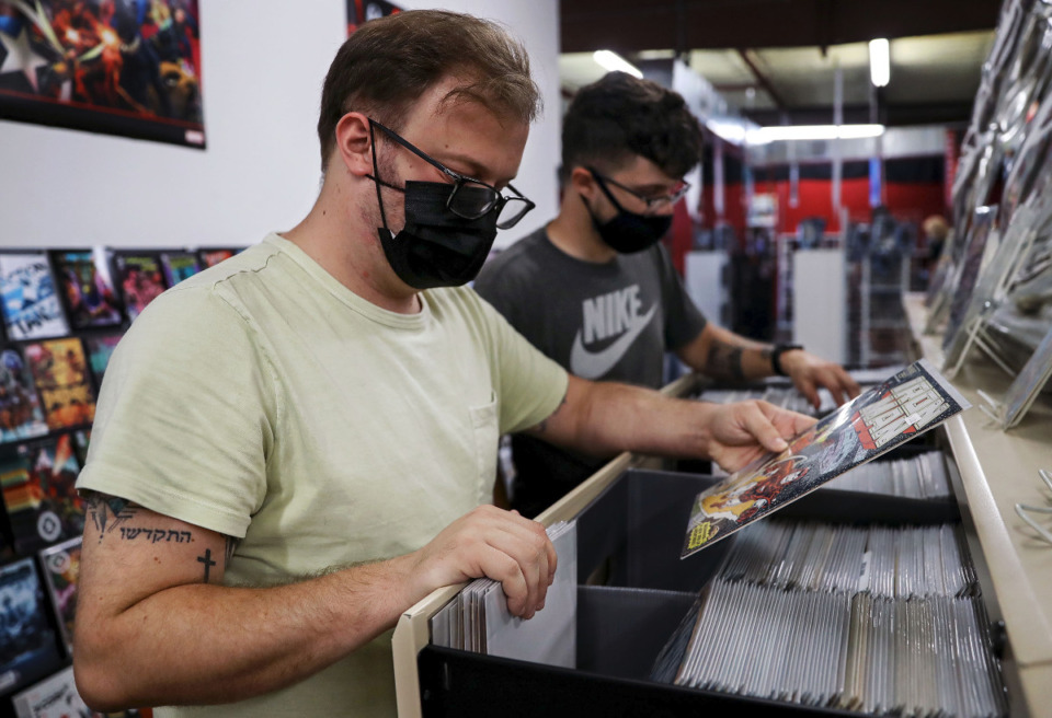 <strong>Micah Timbs (left) and Andrew Hopkins peruse through a collection of classic comics at 901 Comics&rsquo; new location in Cordova.</strong> (Patrick Lantrip/Daily Memphian)