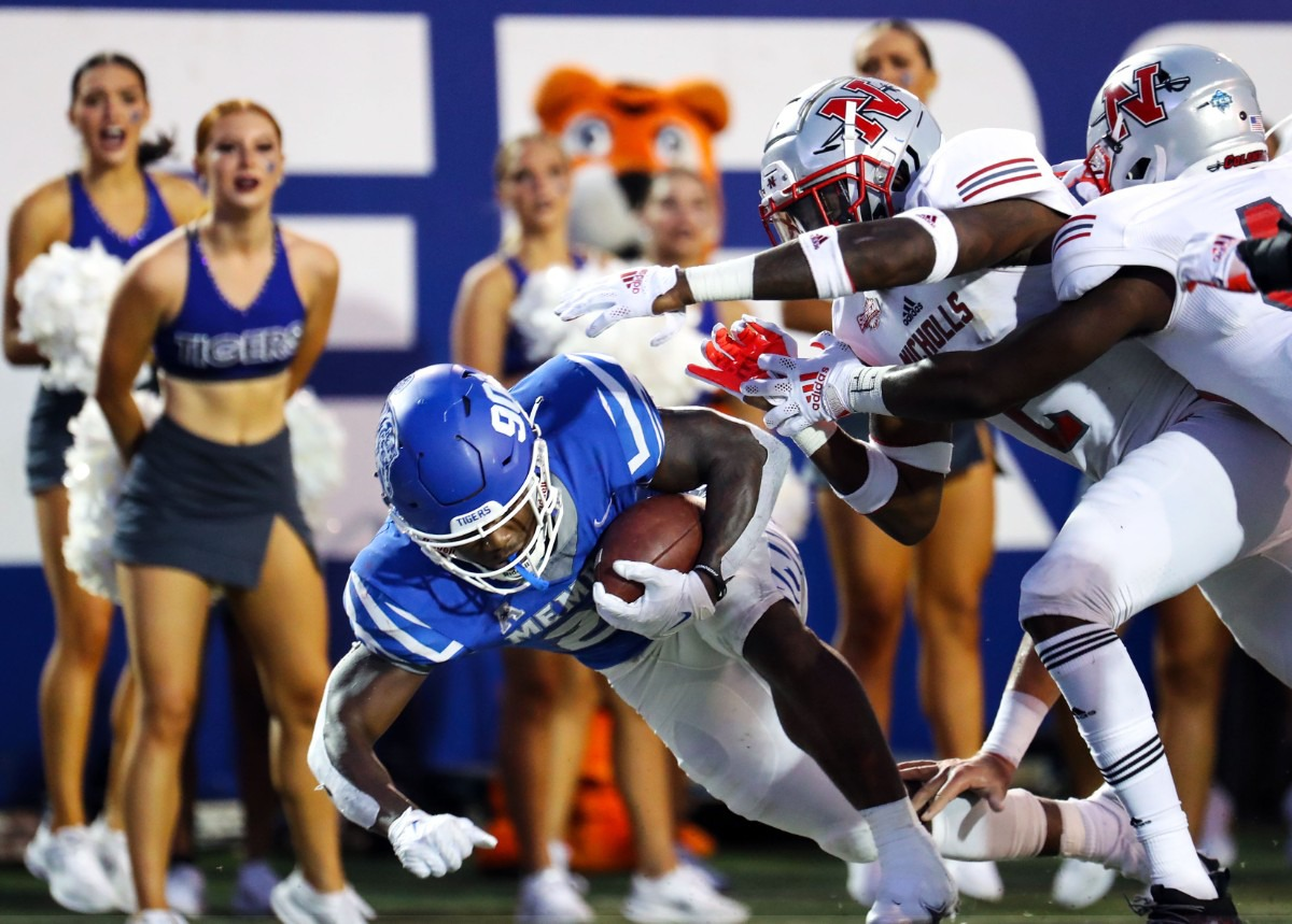 <strong>Running back Brandon Thomas fends off Nicholls State players&rsquo; attempts to grab the ball.</strong> (Patrick Lantrip/Daily Memphian)