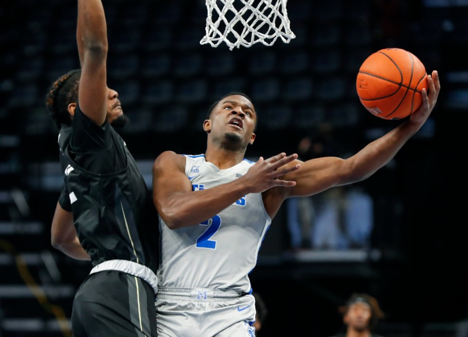 <strong>Tigers guard Alex Lomax (right) drives to the basket against UCF defender Darius Perry (left) in February 2021.</strong> (Mark Weber/The Daily Memphian file)
