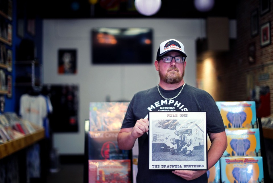 <strong>Chris Braswell holds a copy of an Braswell Brothers album, a country music group consisting of his father and two uncles, inside his downtown record store, River City Records, Sept. 7, 2021.</strong> (Patrick Lantrip/Daily Memphian)