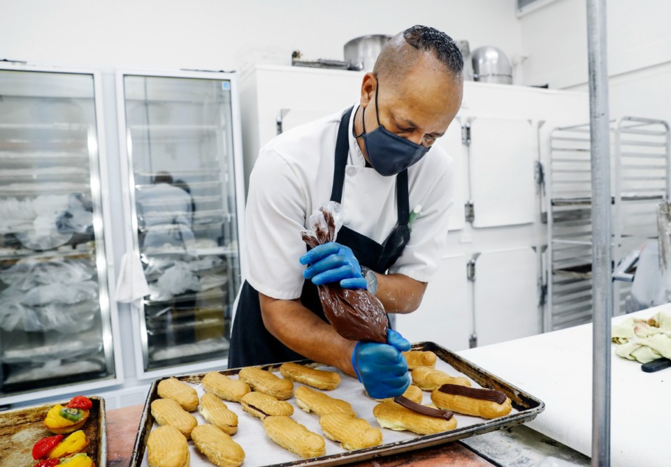 <strong>La Baguette baker Kevin White decorates eclairs on Wednesday, Sept. 8, at the newly reopened bakery.</strong> (Mark Weber/Daily Memphian)