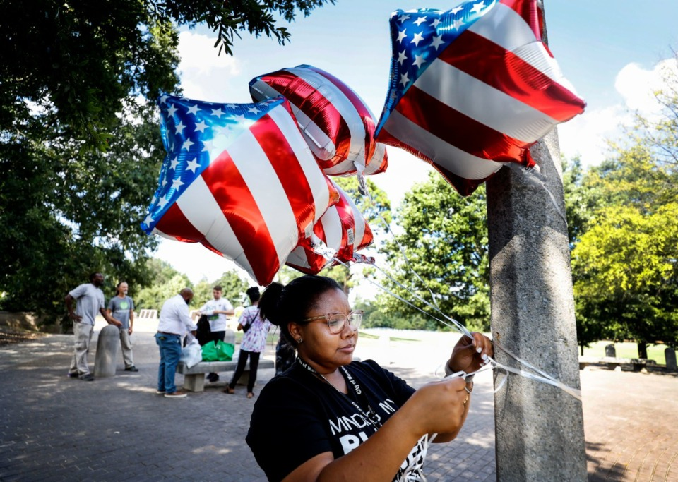 <strong>On the anniversary of 9/11, Kianah Moore hangs America-themed balloons from a pole in Overton Park, before she and other volunteers pick up trash while participating in a day of service and remembrance Wednesday, Sept. 11, 2019.</strong> (Mark Weber/Daily Memphian)