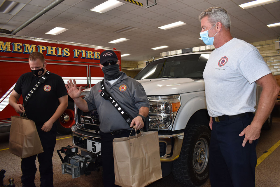 <strong>Lt. Keith Totty hands food donated from Amerigo Italian Restaurant to Lt. Jason Boswell and Private Jonathan Hay of Engine 1 at Fire Station 2 on South Main Street.</strong> (Julia Baker/Daily Memphian)