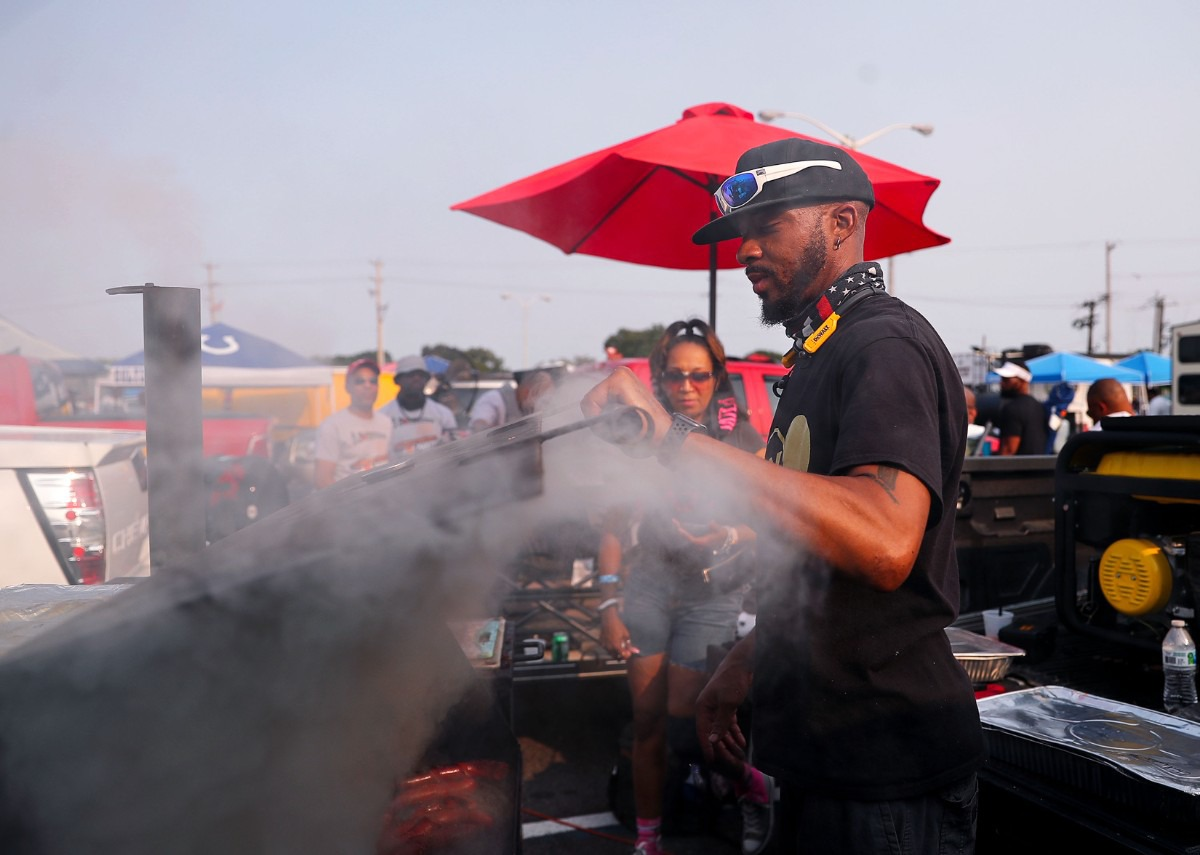<strong>Audric Simmons cooks hotdogs and chicken wings while tailgating before the Southern Heritage Classic.</strong> (Patrick Lantrip/Daily Memphian)