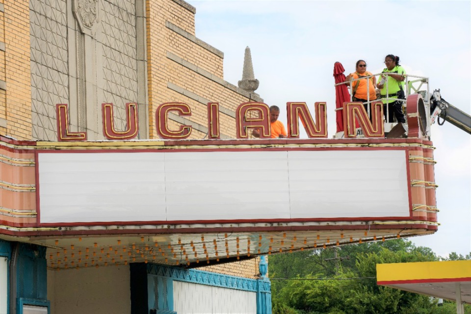<strong>Frank Balton Sign Company installers Francisco Patino (kneeling) and his daughters Esmeralda Patino (orange shirt) and Michelle Patino install the newly made&nbsp;&ldquo;Luciann&rdquo; sign atop the marquee on Wednesday, Sept. 15.</strong> (Tom Bailey/Daily Memphian)