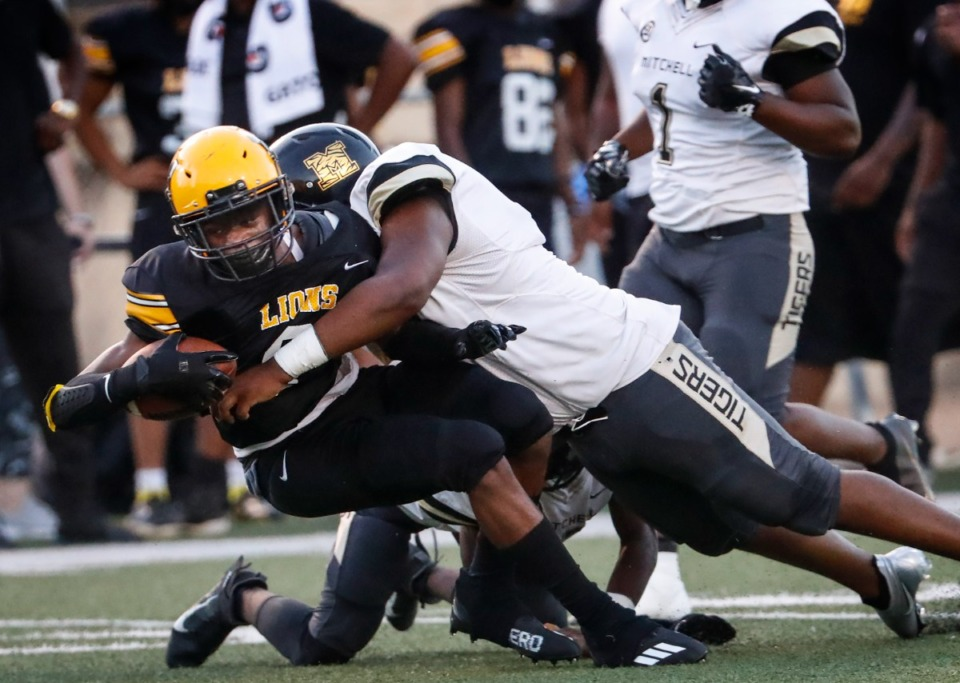 <strong>MAHS running back Kumaro Brown is tackled by the Mitchell defense on Thursday, Sept. 16, 2021.</strong> (Mark Weber/The Daily Memphian)