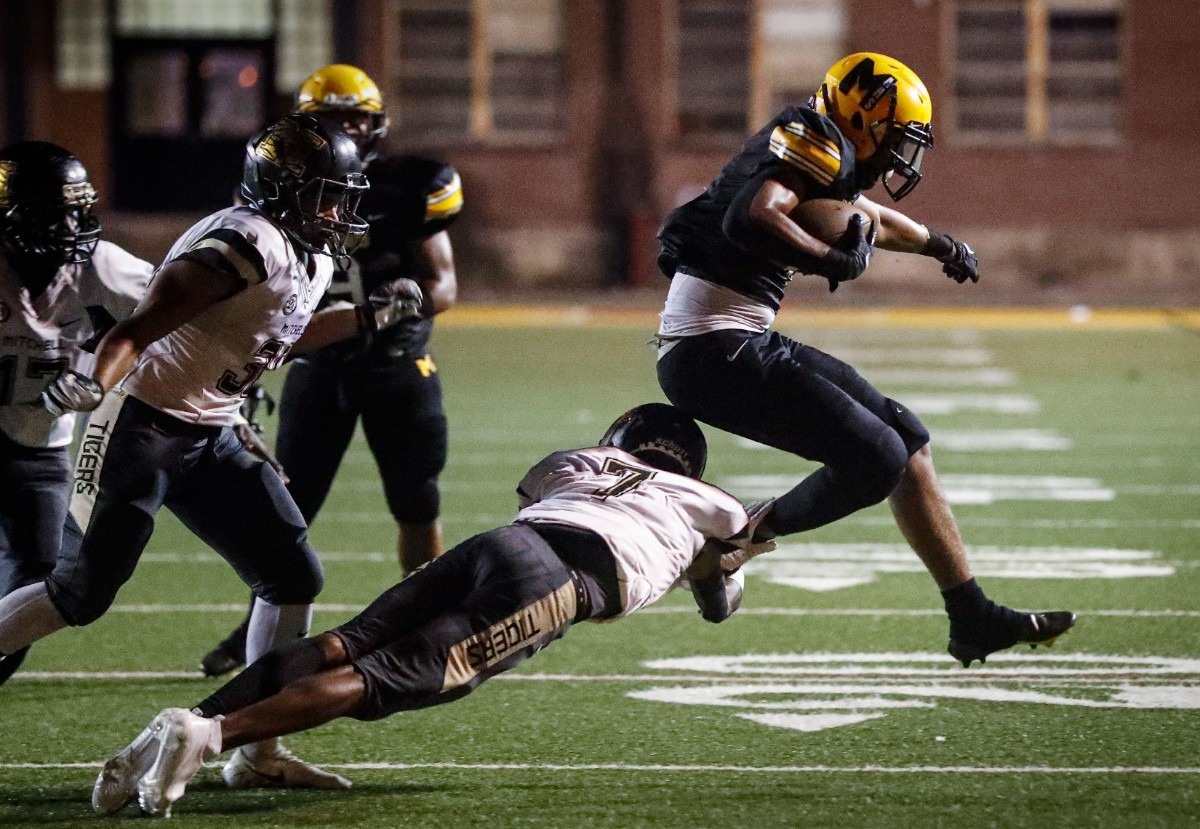 <strong>MAHS running back Cameron Miller (right) eludes Mitchell&rsquo;s Joseph Adams (middle) on Thursday, Sept. 16, 2021.</strong> (Mark Weber/The Daily Memphian)