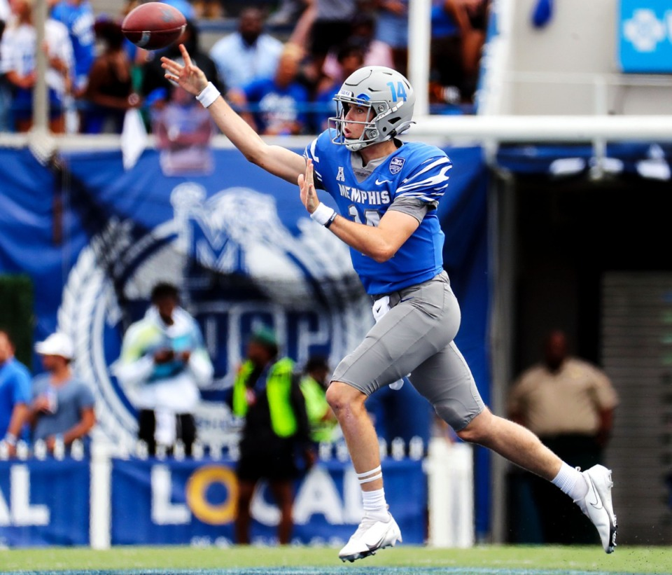 <strong>University of Memphis quarterback Seth Henigan (14) rolls out of the pocket to complete a pass Saturday against Mississippi State University.</strong> (Patrick Lantrip/Daily Memphian)