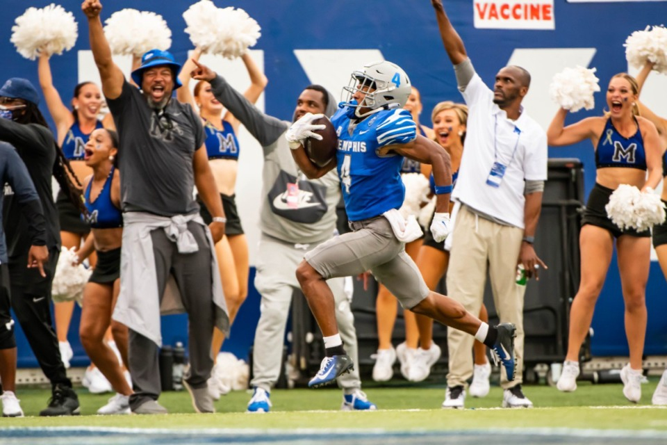<strong>Pro Hall of Famer Isaac Bruce (right, in white shirt) cheers as University of Memphis wide receiver Calvin Austin III (4) makes a touchdown during the Memphis vs. Mississippi State Football game Saturday, Sept. 18, 2021.</strong> (Matthew A. Smith/Memphis Athletics)