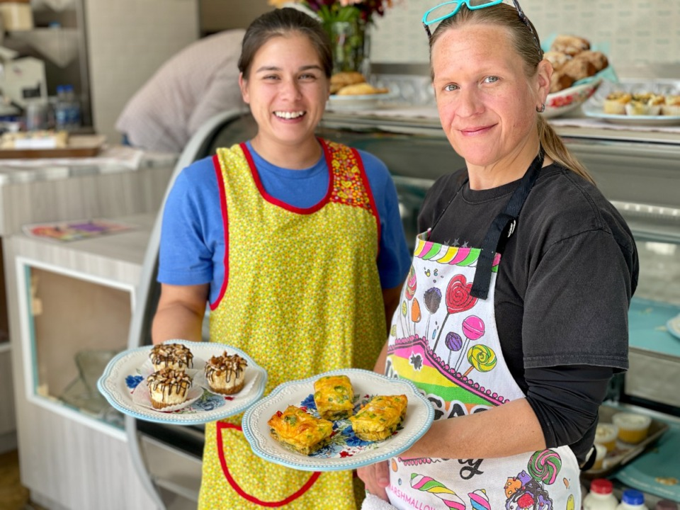 <strong>Anna Beatty (left) and Jenny Riley are the bakers at the reopened Two Girls and a Whip. Beatty holds turtle cheesecake and Riley has crustless quiche.</strong> (Jennifer Biggs/The Daily Memphian)