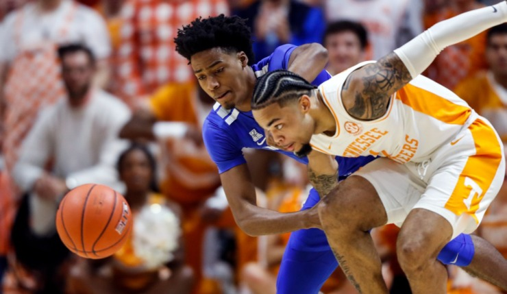 Lamonte Turner (1) battles for the loose ball with Memphis guard Jayden Hardaway (25) during the first half of an NCAA college basketball game Saturday, Dec. 14, 2019, in Knoxville, Tennessee. (AP Photo/Wade Payne)