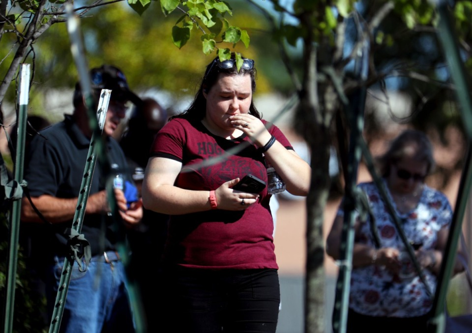 <strong>A survivor of the mass shooting at a Kroger in Collierville checks her phone at the crime scene on Sept. 23, 2021.</strong> (Patrick Lantrip/Daily Memphian)