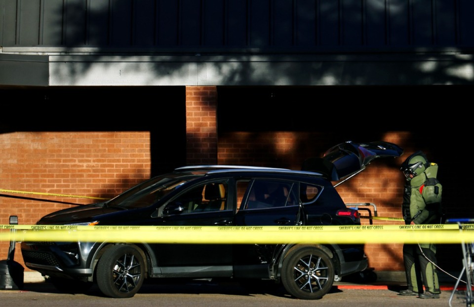 <strong>A member of the bomb squad inspects the vehicle of the suspect believed to be responsible for the mass shooting at a Kroger in Collierville on Sept. 23, 2021.</strong> (Patrick Lantrip/Daily Memphian)