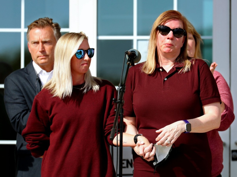 <strong>Hollie Skaggs (right) holds the hand of Sara Wiles while she speaks at a Sept. 24, 2021, vigil at Collierville Town Hall for the victims of the Kroger shooting in Collierville.</strong> (Patrick Lantrip/Daily Memphian)