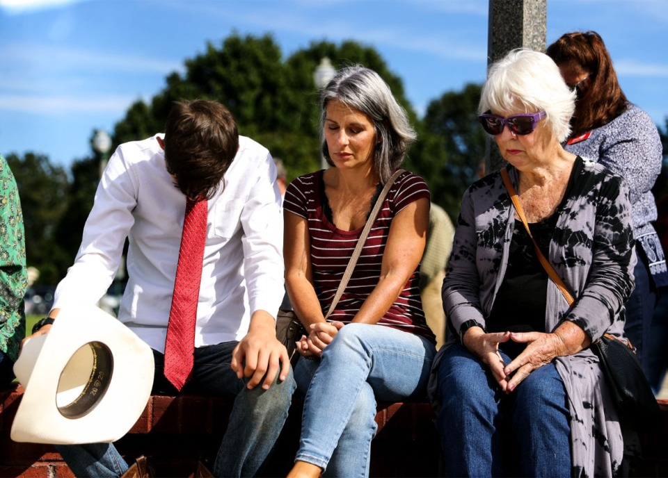 <strong>Noah Gervase, Maria Gervase and Peggy Harwell bow their heads in prayer during a Sept. 24, 2021, vigil at Collierville Town Hall for the victims of the Kroger shooting in Collierville.</strong> (Patrick Lantrip/Daily Memphian)