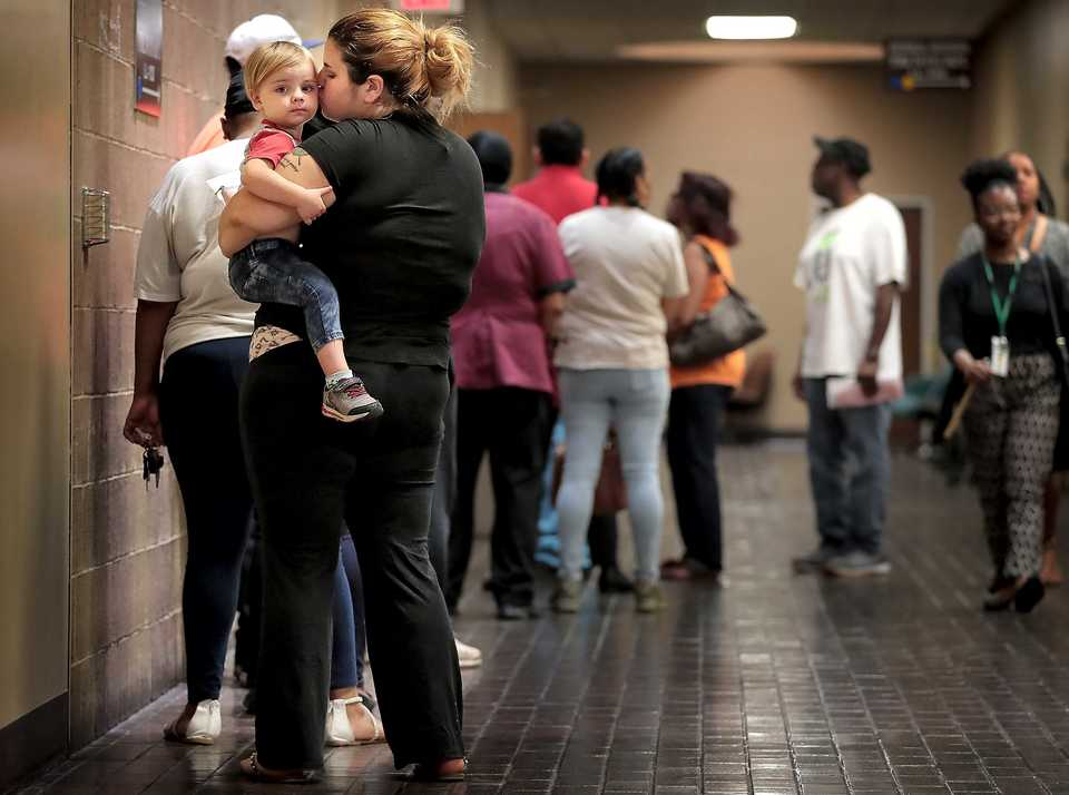 <strong>Caitlin Mayo and her son, Declan, 2, wait in line for traffic court on Monday, Aug. 13. Rising traffic and license fees are a heavy burden for many Memphians,&nbsp; creating an impossible situation for many working poor who can't pay their fees without work and can't find work without a driver's license.</strong> (Jim Weber/Daily Memphian)