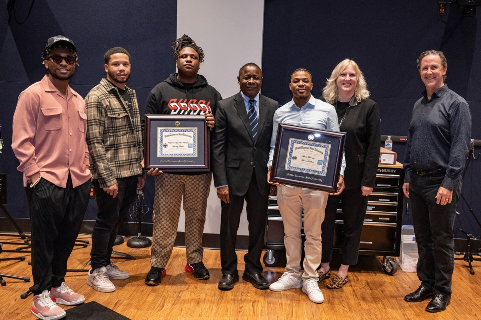 <strong>Brytavious &ldquo;Tay Keith&rdquo; Chambers, third from left, holds the honorary professorship certificate he was presented from Middle Tennessee State University. Pictured, from left, is alumnus Tyland Jackson, Chambers&rsquo; stylist; Chambers&rsquo; manager Cambrian Strong; Chambers; MTSU President Sidney A. McPhee; Drumatized Executive, Chambers&rsquo; PR director and MTSU alumnus Nicholas Brownlow, who was also honored; College of Media and Entertainment Dean Beverly Keel; and John Merchant, chair of the Department of Recording Industry.</strong> (Photo by Cat Curtis Murphy)