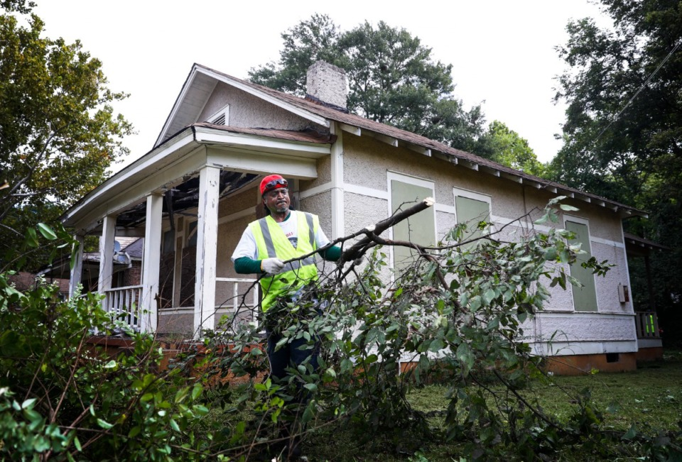 <strong>Tarik Tate clears overgrown brush outside the house at 852 Alaska St., on Monday, Sept. 20. Crews are clearing 150 lots acquired by the Klondike/Smokey City CDC with the help of Neighborhood Preservation Inc. and The Works.</strong> (Mark Weber/Daily Memphian)