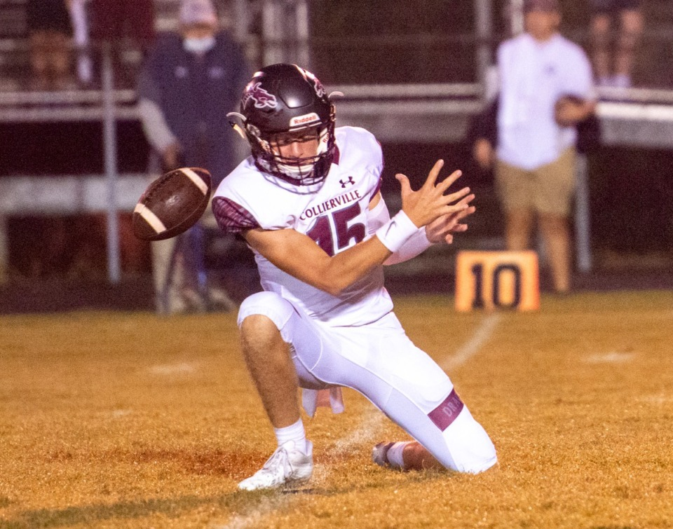 <strong>A wet ball slips through the hands of Collierville High School junior quarterback Logan Johns on the extra point early in the first quarter of the game against Germantown.</strong> (Greg Campbell/Special to The Daily Memphian)