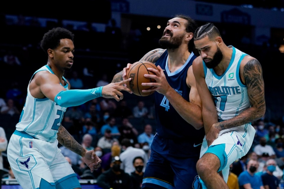 <strong>Memphis Grizzlies' Steven Adams drives to the basket between Charlotte forwards P.J. Washington, left, and Cody Martin&nbsp; on Oct. 7, 2021, in Charlotte, North Carolina.</strong> (Chris Carlson/AP)