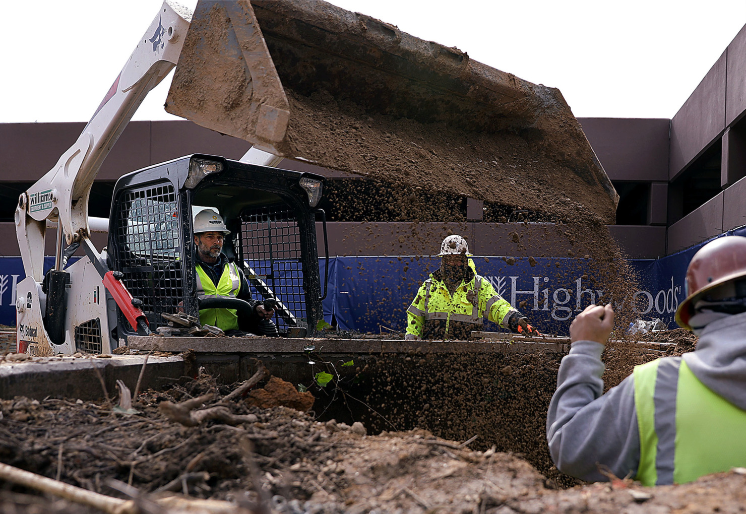 <strong>Phillip McCullough dumps a load of dirt into a freshly excavated hole with the help of Eduardo Olvera and Rojelio Olvera on Thursday, Feb. 14, 2019. The men were working on overhauling the Crescent Center's landscaping.</strong> (Patrick Lantrip/Daily Memphian)