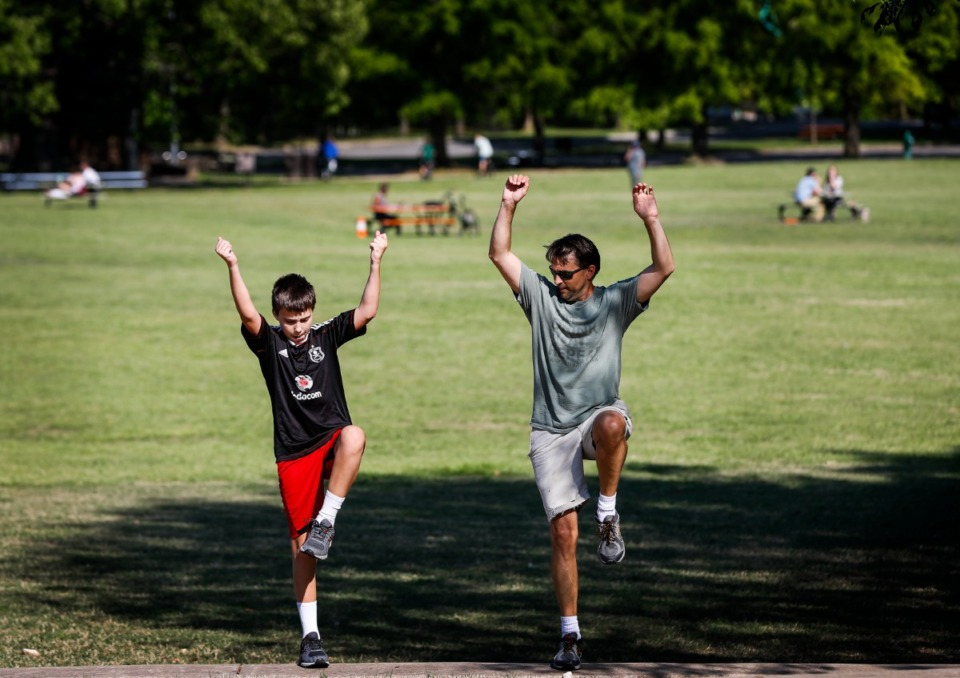 <strong>Hayden Weeks, 13, (left) exercises with his father Matt (right) in Overton Park on Monday, April 20, 2020.</strong> (Mark Weber/Daily Memphian)
