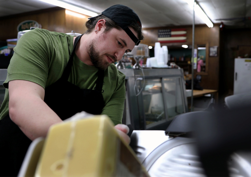 <strong>Hunter Greer slices up a fresh block of cheese at Bogie's Delicatessen on Mendenhall in East Memphis Monday, Feb. 18, 2019. Landlord Boyle Investment Co. is exploring a redevelopment of Williamsburg Village, the 54-year-old shopping center Bogie's calls home.</strong>&nbsp;(Patrick Lantrip/Daily Memphian)