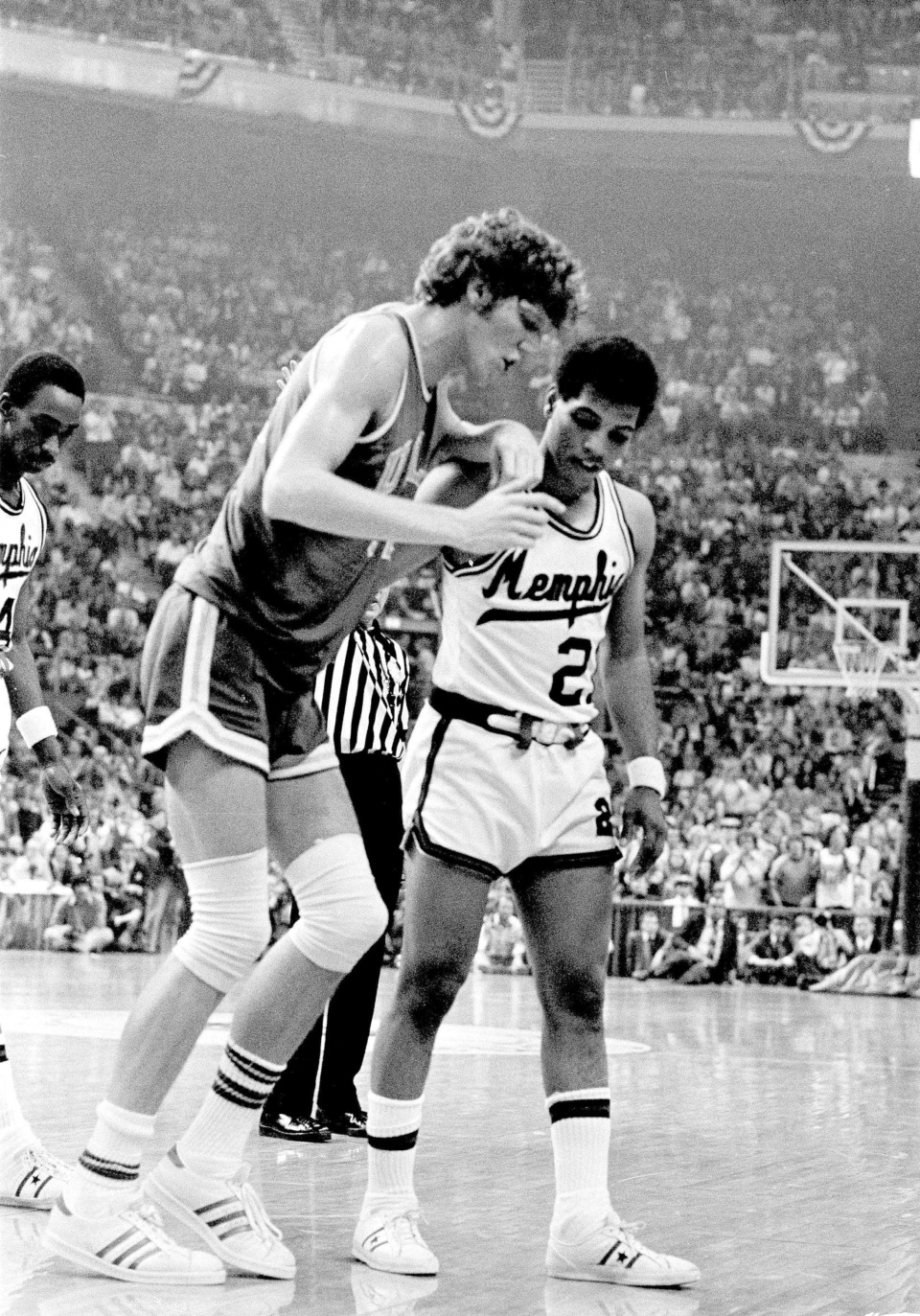 <strong>Larry Finch, during his playing days at Memphis State University, helps UCLA center Bill Walton off the floor during the 1973 NCAA Championship game.</strong> (Associated Press file photo)