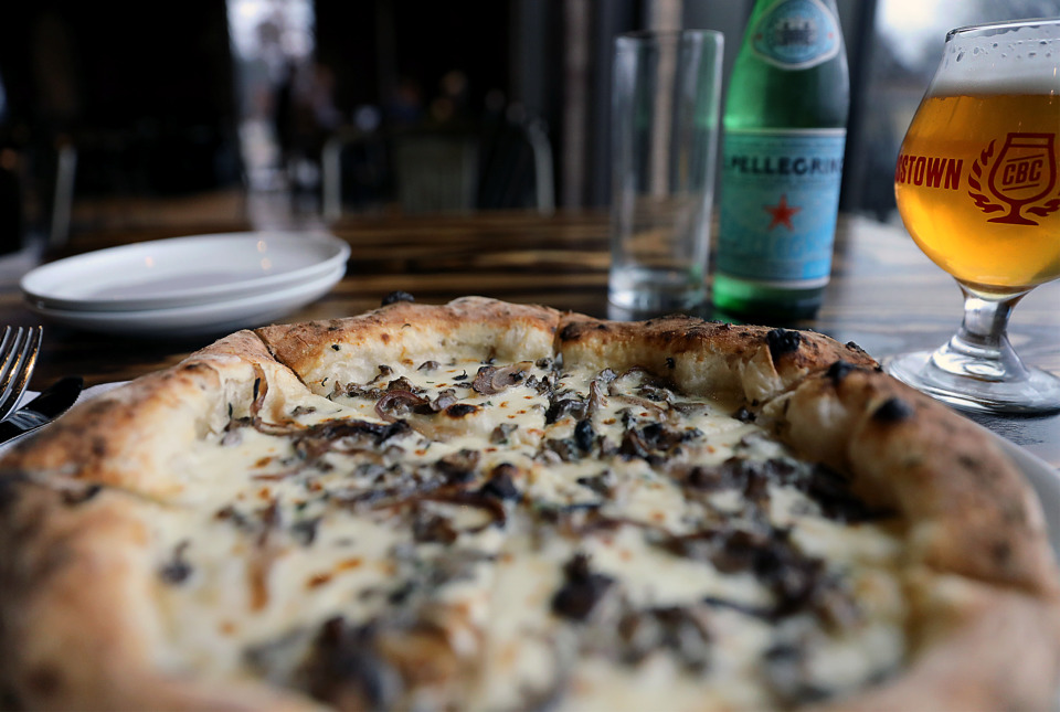<strong>The Forager is topped with crema, fresh mozzarella, parmesan, roasted onions and an earthy trio of cremini, portobello and oyster mushrooms. It's packed with flavor and it's served without a tomato sauce.</strong> (Patrick Lantrip/Daily Memphian)