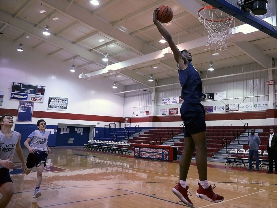 <strong>Even though Tipton-Rosemark Academy sophomore Alex Anderson is still getting used to the upper limits of his high-flying, post-growth abilities, he had no trouble hammering home a dunk during practice Wednesday, Feb. 20, 2019, while his father, TRA coach Cedric Anderson, looks on from the sideline.</strong> (Patrick Lantrip/Daily Memphian)