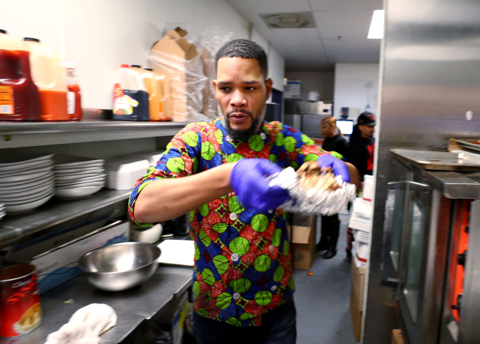 <strong>Elijah Townsend, a chef at Sage Restaurant on South Main Street, pulls a philly cheese steak baked potato from the oven during lunch hour. The business is one of 14 black-owned restaurants taking part in the largest Memphis Black Restaurant Week to date.</strong> (Houston Cofield/Daily Memphian)