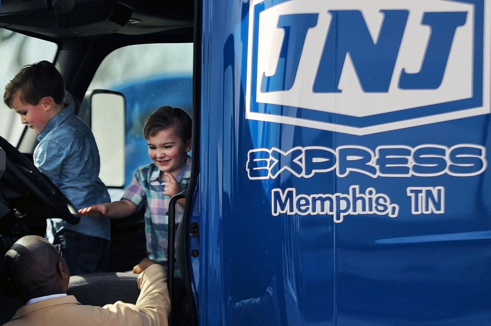 <strong>Grayson and Easton Ennis, the sons of JNJ Express CEO John Ennis Jr., play in the cab of one of their father's trucks under the watchful eye of longtime employee Lester Lawson on Tuesday, Feb. 26.&nbsp;The transportation company, which was founded in Memphis 27 years ago, is moving its headquarters, operations center, vehicle maintenance facility and cross dock to a vacant Parkway Village shopping center.</strong> (Patrick Lantrip/Daily Memphian)