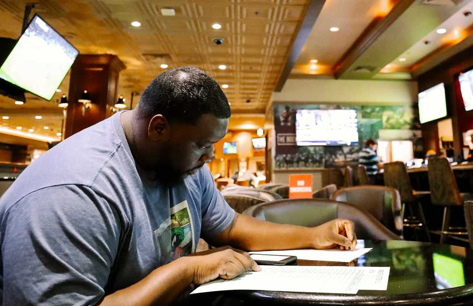 "<strong>Mario McKillion places bets on football at the Horseshoe Casino's new sports betting lounge. ""I like taking the underdog team, having the points on my side,"" he said. ""They don't have to win the game. I'm big on that.""</strong> (Houston Cofield/Daily Memphian)"