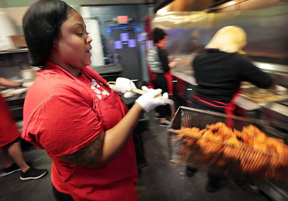 "Brittney Thrash calls out "" Hot chicken!"" in the kitchen as she pulls baskets of fried chicken for the lunch rush on September 11, 2018 at the Gus's Fried Chicken in downtown Memphis. (Jim Weber/Daily Memphian)"