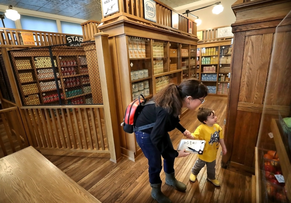 <strong>Liz Marlow and her son Ryan Malow, 3, hunt through the Piggly Wiggly exhibit at the Pink Palace Museum, looking for a checklist of dry goods on Feb. 28, 2019. Founded in Memphis by Clarence Saunders in 1916, Piggly Wiggly was the first self-service grocery store with shopping carts, individual pricing and check-out counters.</strong> (Jim Weber/Daily Memphian)