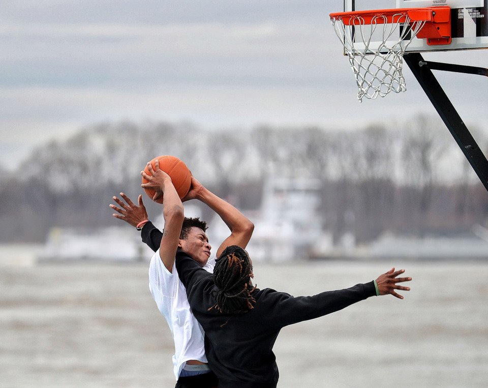 <strong>Cortavius Thompson (left) and Duke Warren play a game of one-on-one at the pop-up park in the parking lot of Beale Street Landing as barge traffic passes by on the Mississippi River. </strong>&nbsp;(Jim Weber/Daily Memphian)