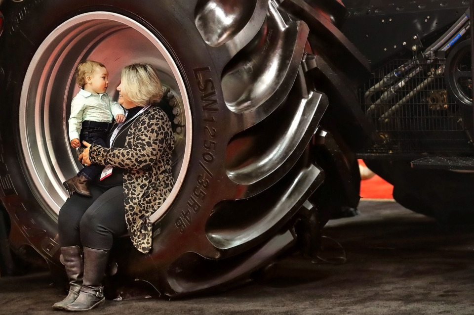 <strong>Regina Kern and her 1-year-old grandson Knox Graham take a break on a combine wheel while looking around at the farm equipment on display during the 67th annual Mid-South Farm &amp; Gin Show at the Memphis Convention Center. Farmers from around the region gathered to attend seminars, learn about trends in the industry and view new technology and equipment.</strong> (Jim Weber/Daily Memphian)