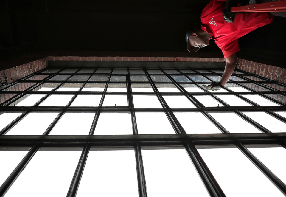 <strong>Eric Thornton cleans the windows at the new Malco Powerhouse theater on Thursday, March 7, 2019, as contractors and Malco employees make a few final adjustments and improvements before the opening of the Downtown theater, which features a restaurant with in-theater delivery and reserved luxury seating.</strong> (Jim Weber/Daily Memphian)