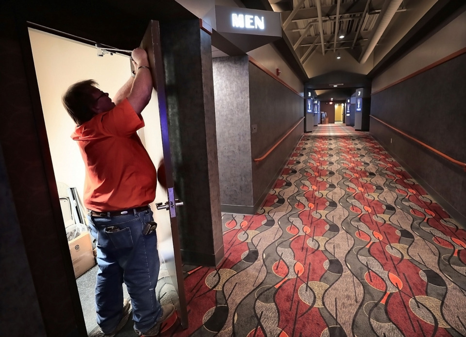 <strong>Billy Clark adjusts doors at the new Malco Powerhouse theater on Thursday, March 7, 2019, as contractors and Malco employees make a few final adjustments and improvements before the opening of the Downtown Memphis theater.</strong> (Jim Weber/Daily Memphian)