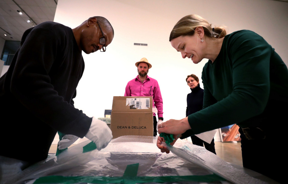 "<strong>George Burton (left), gallery assistant at the University of Memphis Art Museum, and Jennifer Draffen (right), assistant director of the museum, unwrap a piece of art to hang in the ""Dear Artist"" exhibition. The show features works acquired by Memphis-based art collectors. </strong>&nbsp;(Houston Cofield/Daily Memphian)"